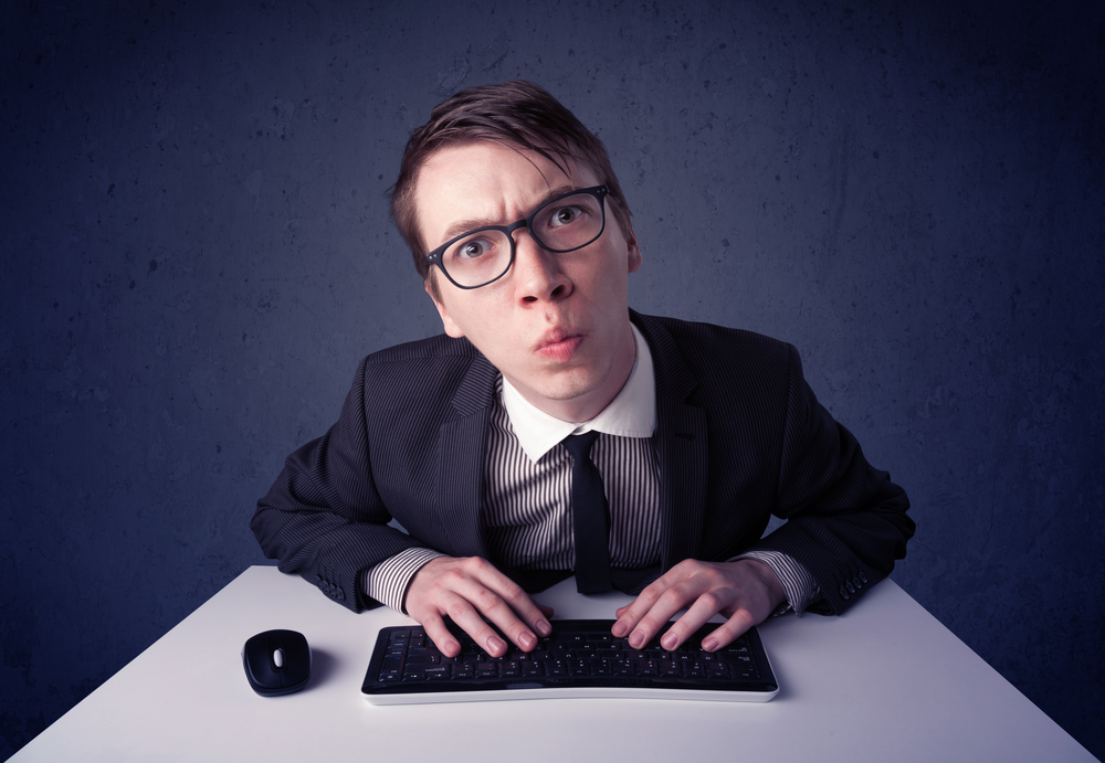 Hacker working with keyboard and mouse on blue background