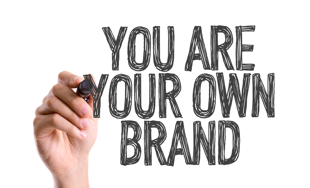 Hand with marker writing You Are Your Own Brand