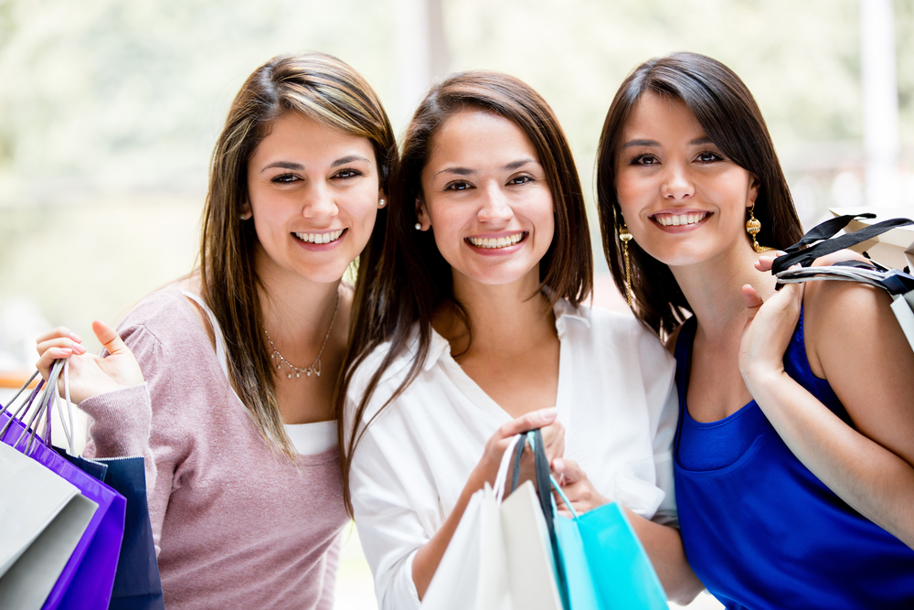Happy group of female friends shopping holding bags