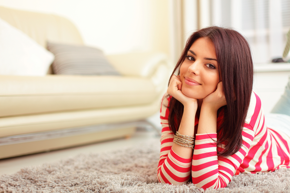 Smiling teen girl in colorful cloths lying on floor and relaxing